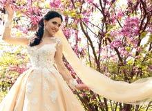 La jeune mariée magnifique dans la robe de mariage et la couronne posant en été de fleur font du jardinage photos stock