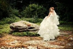 La jeune mariée magnifique dans une robe blanche luxuriante danse photographie stock libre de droits