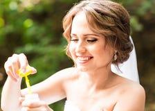 La jeune mariée magnifique heureuse ont l'amusement avec le ventilateur de bulle dehors dans le parc Image stock