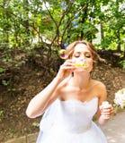 La jeune mariée magnifique heureuse ont l'amusement avec le ventilateur de bulle dehors dans le parc Images libres de droits