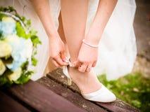 La jeune mariée met dessus la chaussure photo libre de droits