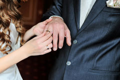 La jeune mariée met l'anneau de mariage sur le doigt de marié le jour de la cérémonie de mariage Image stock