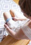La jeune mariée met sur la jarretière Image libre de droits