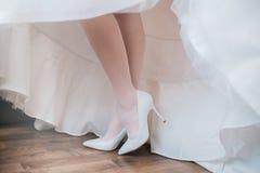 La jeune mariée met sur ses chaussures photos libres de droits