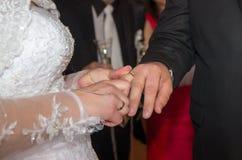 La jeune mariée met un anneau de mariage sur le marié Photographie stock