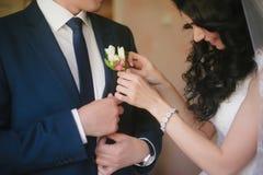 La jeune mariée orne le marié de costume de mariage de boutonnière, mariage, célébration, fleurs, marié, jeune mariée, mode de vi image stock