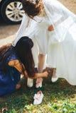 La jeune mariée porte la chaussure Image stock