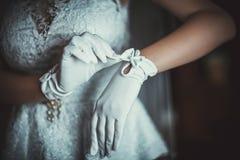 La jeune mariée porte des gants de mariage avec un arc sur des mains sur la préparation de matin de robe de mariage pour le maria photo stock