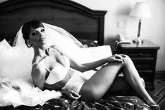La jeune mariée pose dans la blancheur sur le lit de fond images stock