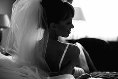 La jeune mariée pose dans la blancheur sur le lit de fond photo stock