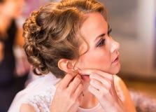 La jeune mariée prend les boucles d'oreille, épousant la préparation images libres de droits