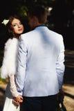 La jeune mariée regarde au-dessus de l'épaule de son fiancé tandis que la promenade photo stock