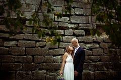 La jeune mariée regarde dans les yeux du marié tandis qu'ils se tiennent derrière une vieille pierre Image libre de droits