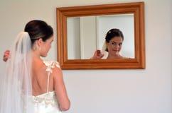 La jeune mariée regarde elle-même dans le miroir son jour du mariage Image stock