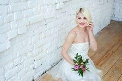 La jeune mariée s'assied à un mur blanc image libre de droits