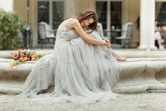 La jeune mariée s'assied près du vintage de fontaine Images stock