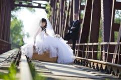 La jeune mariée s'assied sur une valise Image stock