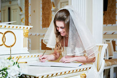 La jeune mariée se connecte l'enregistrement solennel du mariage Images stock