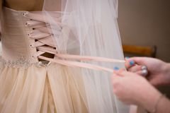La jeune mariée se prépare à la cérémonie Les mains ont noué le ruban sur le corset images stock