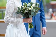 La jeune mariée se tient avec la jeune mariée et tient un bouquet Photographie stock libre de droits