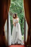 La jeune mariée se tient près de la fenêtre photos libres de droits