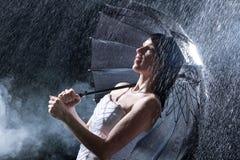 La jeune mariée se tient sur la forte pluie en retard la nuit. Photos stock