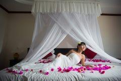 La jeune mariée se trouve sur le lit dans la chambre d'hôtel photo libre de droits