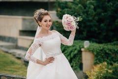 La jeune mariée se vante à ses amies avec un bouquet futé des pivoines Une fille dans une robe de mariage, voile et avec une cour Photo libre de droits