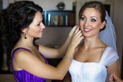La jeune mariée semble drôle tandis que la demoiselle d'honneur ajuste une boucle d'oreille Image libre de droits