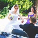 La jeune mariée semble drôle tandis que la demoiselle d'honneur ajuste une boucle d'oreille Images stock
