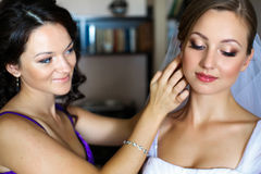 La jeune mariée semble drôle tandis que la demoiselle d'honneur ajuste une boucle d'oreille Photos stock
