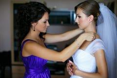 La jeune mariée semble drôle tandis que la demoiselle d'honneur ajuste une boucle d'oreille Photo stock