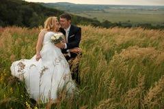 La jeune mariée semble le penchement heureux à un marié sur le champ images libres de droits