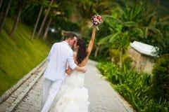 La jeune mariée a soulevé sa main avec un bouquet des fleurs, embrassant le marié en parc images stock