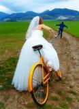 La jeune mariée sur le rétro vélo orange chasse après un marié dans le costume bleu de mariage avec une bouteille à bière Proue d Photo libre de droits