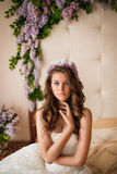 La jeune mariée sur un lit avec un lilas Photos libres de droits