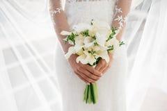 La jeune mariée tenant le beau mariage blanc fleurit le bouquet Images stock