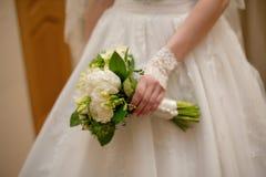 La jeune mariée tenant le bouquet blanc de mariage des roses et l'amour fleurissent Photo stock