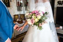 La jeune mariée tenant un bouquet de mariage dans les mains de la BO l'épousant Photo stock