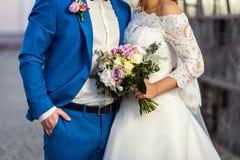 La jeune mariée tenant un bouquet de mariage dans les mains de la BO l'épousant Images libres de droits