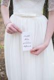 La jeune mariée tenant une carte «amour vient toujours dans le time» Photographie stock