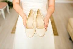 La jeune mariée tient des chaussures de mariage dans des mains Photo stock