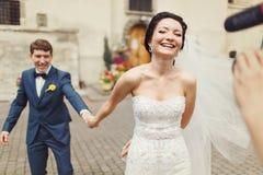 La jeune mariée tient la main du marié marchant avec lui au cameraman Image libre de droits