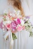 La jeune mariée tient le bouquet de mariage images libres de droits