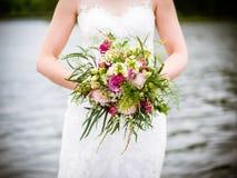 La jeune mariée tient le bouquet nuptiale images libres de droits