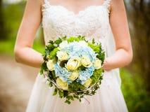 La jeune mariée tient le bouquet nuptiale photographie stock