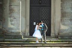 La jeune mariée tient le fiancé pour le lien et l'embrasse sur le fond vieux font Image libre de droits