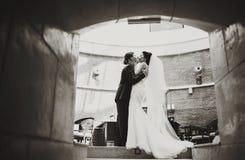 La jeune mariée tient le visage du marié dans des ses bras l'embrassant dans le tunnel photographie stock