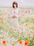 La jeune mariée tient les fleurs de pavot dans le domaine de pavot Images stock