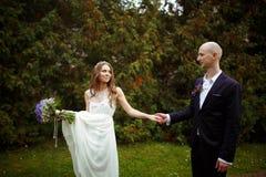 La jeune mariée tient un bouquet et une robe dans une main de bras et de marié dedans Image libre de droits